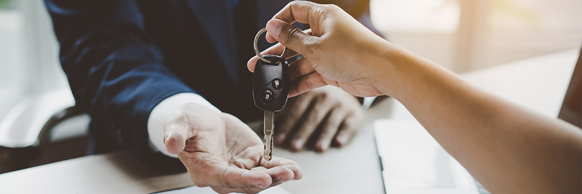 Close up view hand of agent giving car key to customer