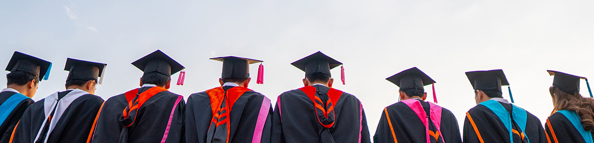 College grads lineup up in caps and gowns