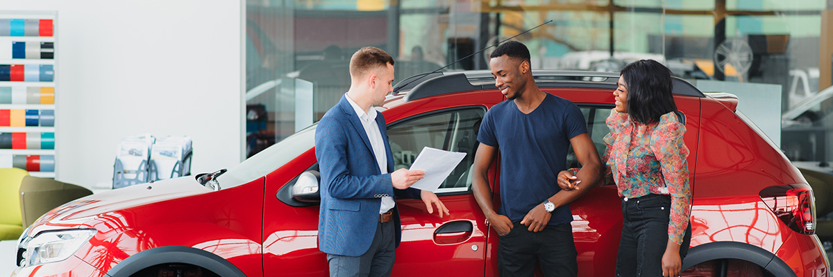 couple and salesperson standing in front of car at a dealership