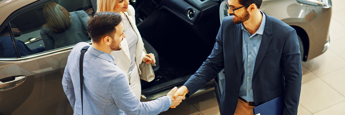 close up view of handshake of salesmen with the man in the showroom on the background of a woman in a new car