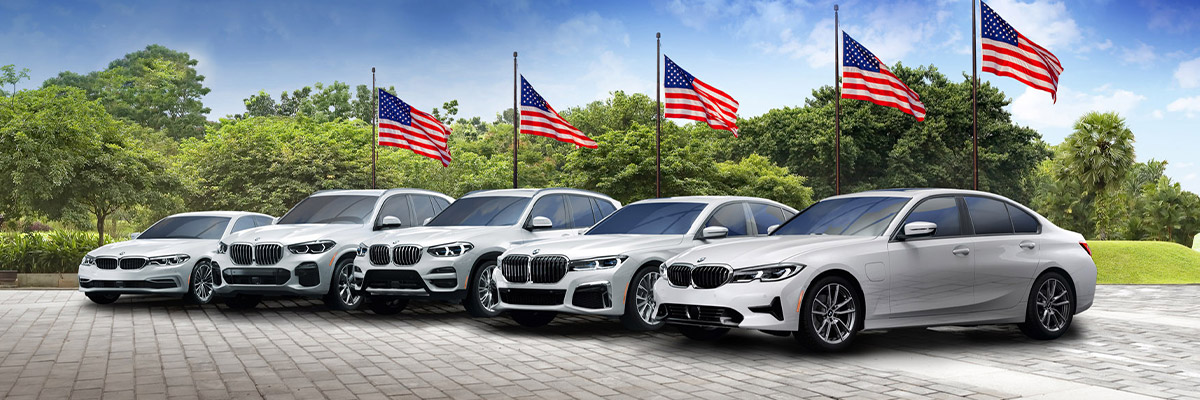 BMW lineup parked next to field with american flags.