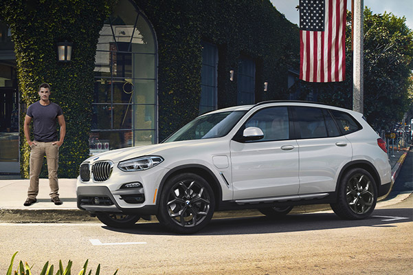 BMW SUV parked on street with american flag.