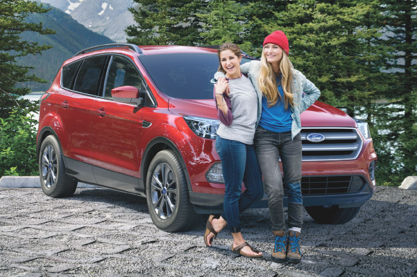 Two young women standing outside their Ford enjoying the scenery