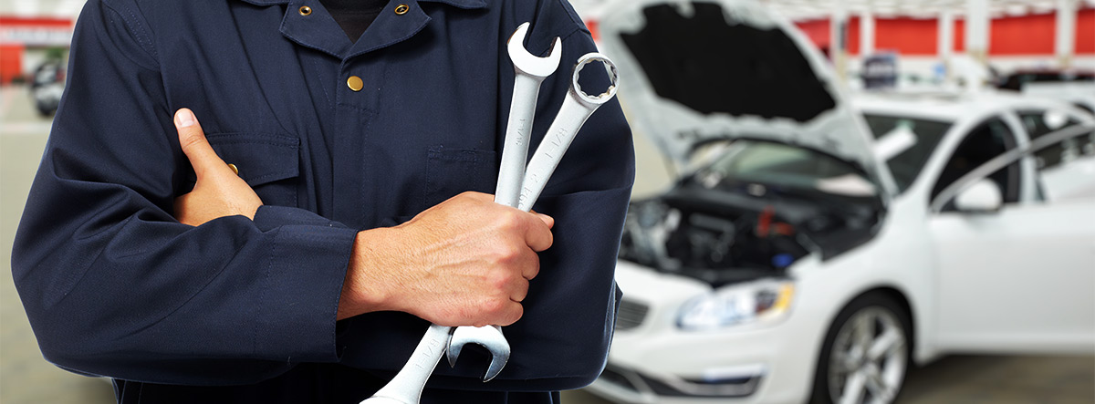 Service man holding wrench with car in the background