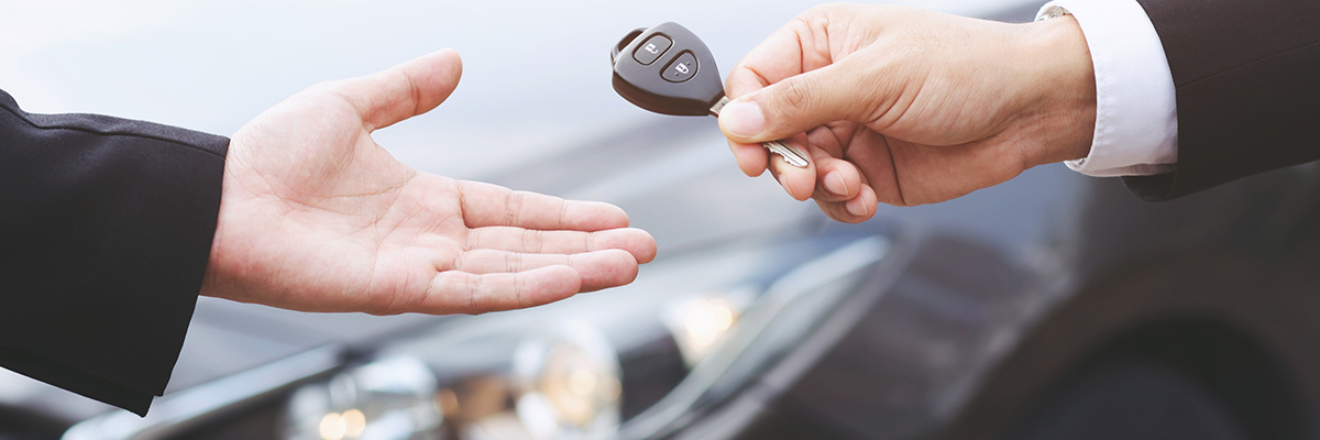 Close up of one person handing a set of car keys over to the other
