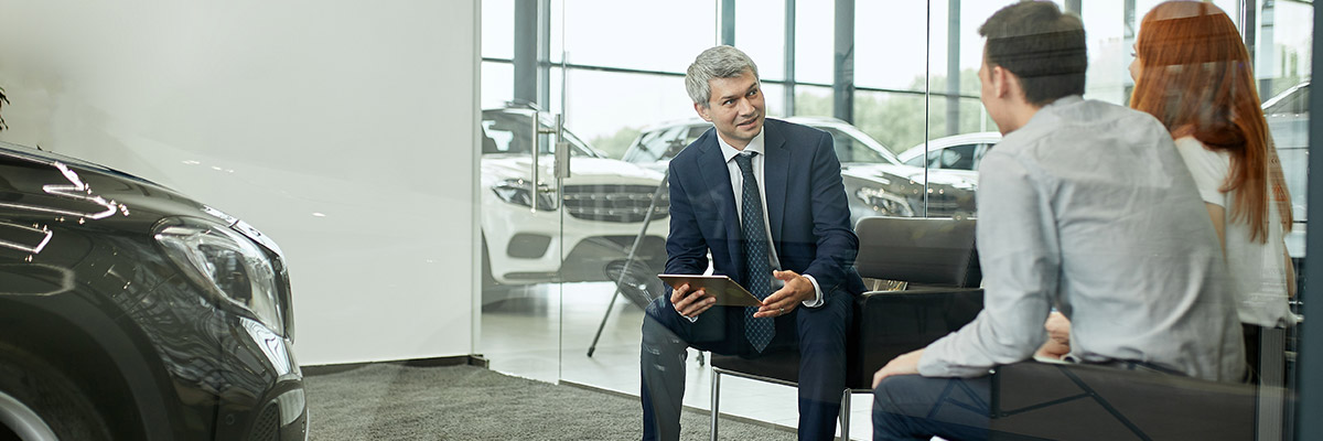 Dealer sitting with couple inside of office